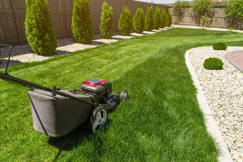 A lawn being mowed to maintain looks and appeal of a house.